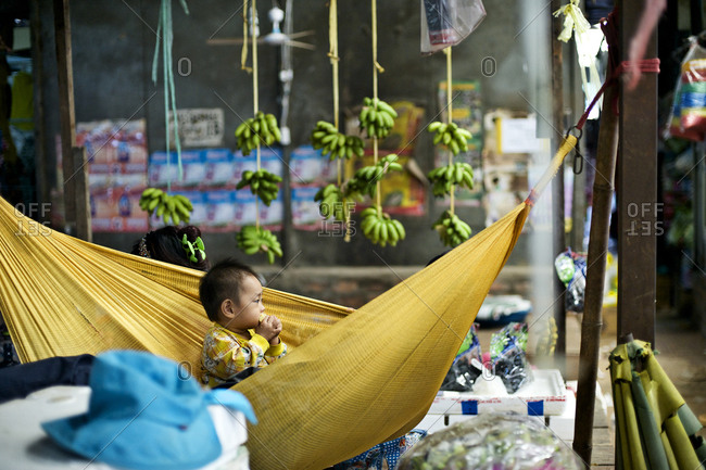 Siem Reap, Cambodia - December 22, 2014: Baby sitting in a hammock at a market