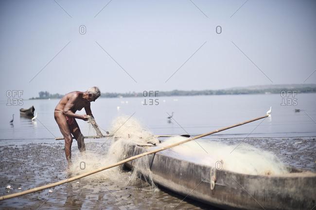 Near Anjuna, Goa, India - January 31, 2015: Fisherman untangling his net