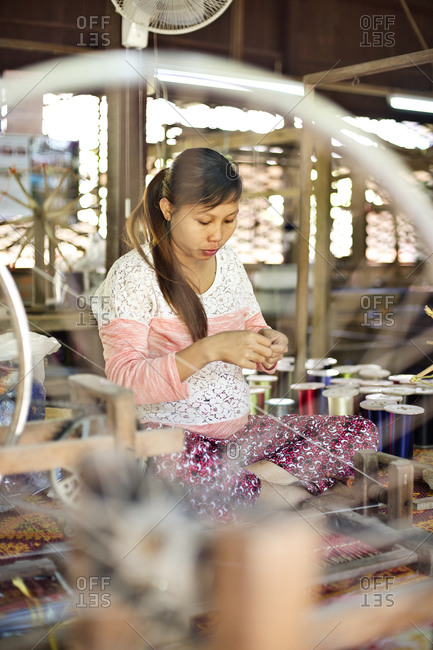 Siem Reap, Cambodia - December 22, 2014: Portrait of woman working in a silk factory