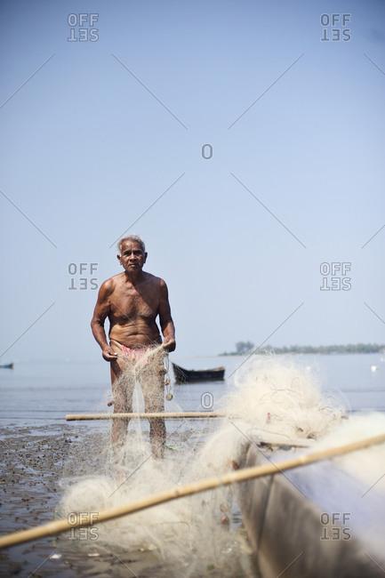 Near Anjuna, Goa, India - January 31, 2015: Portrait of a fisherman with a fishing net