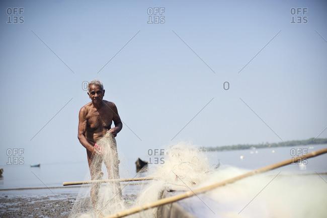 Near Anjuna, Goa, India - January 31, 2015: Fisherman preparing his fishing net