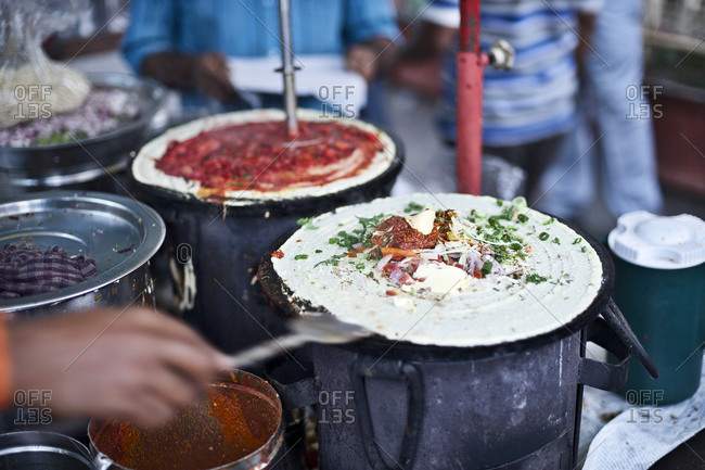 Person cooking dosa on the street