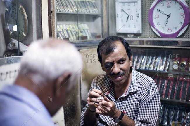 Mumbai, India - February 3, 2015: Jeweler examining a bracelet