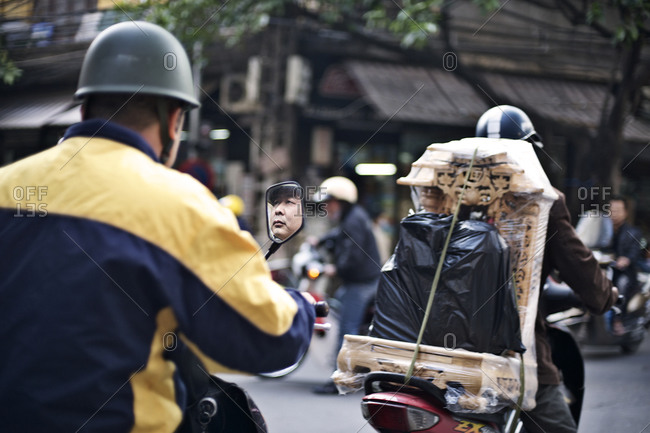 Hanoi, Vietnam - December 29, 2014: People riding scooters on the street