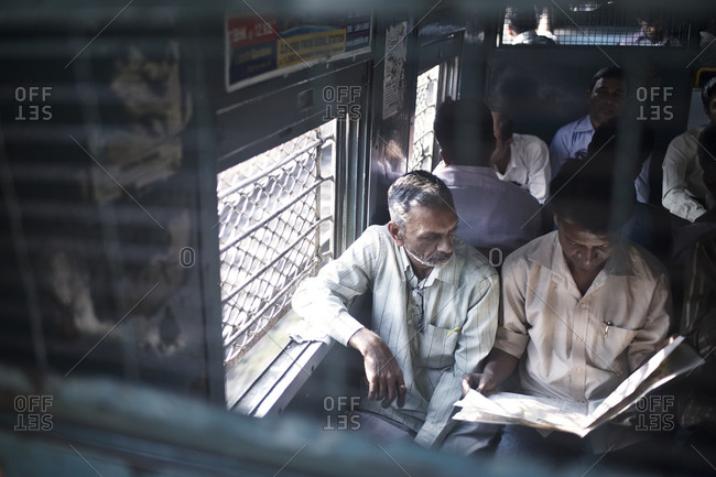 Mumbai, India - February 4, 2015: Man reading a newspaper on a crowded train