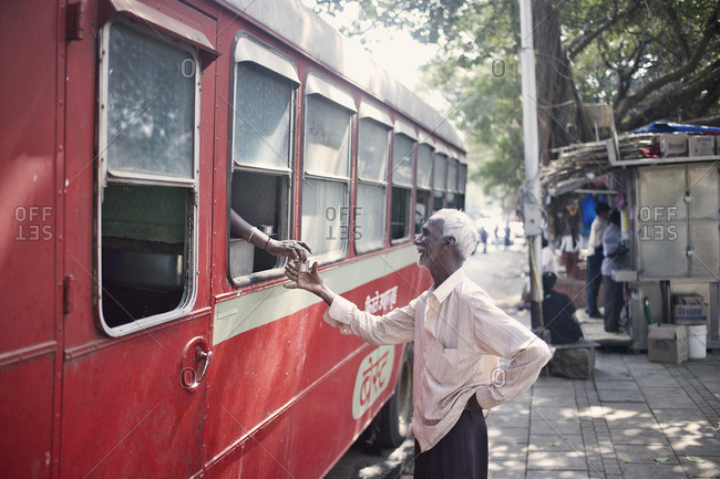 Mumbai, India - February 4, 2015: Man buying a drink from a food truck