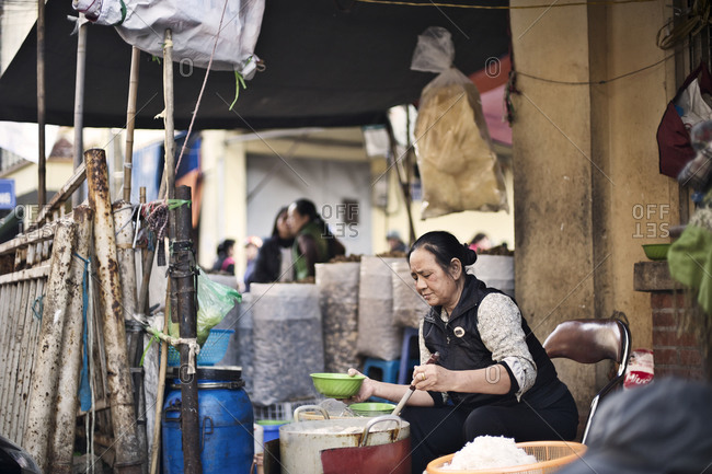 Hanoi, Vietnam - December 29, 2014: Woman cooking food in a market