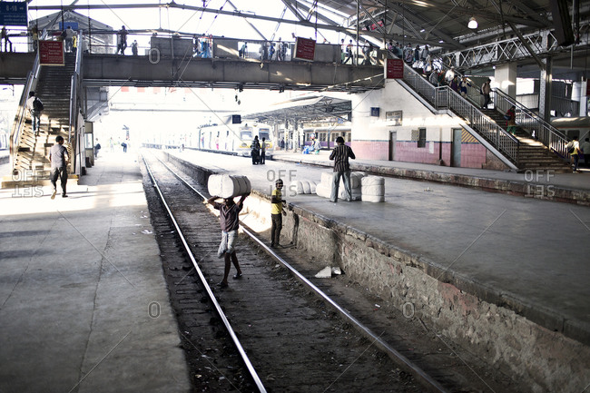 Mumbai, India - February 4, 2015: Men moving packages across train tracks