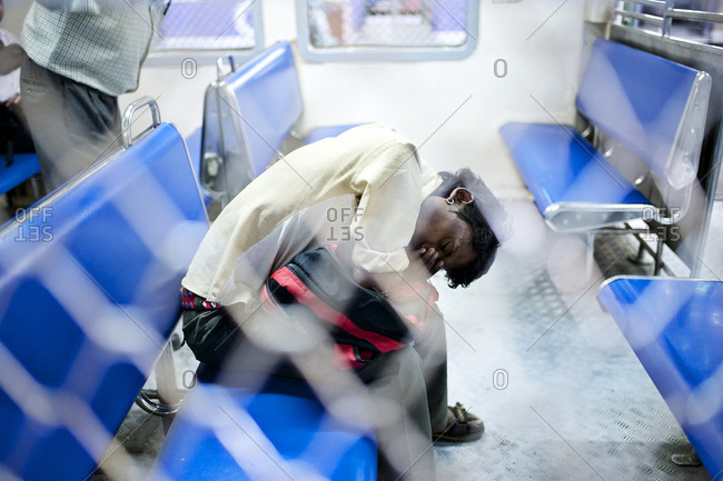 Mumbai, India - February 4, 2015: Man fallen asleep on a train