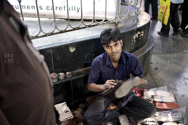 Mumbai, India - February 4, 2015: Shoe shiner working on the street