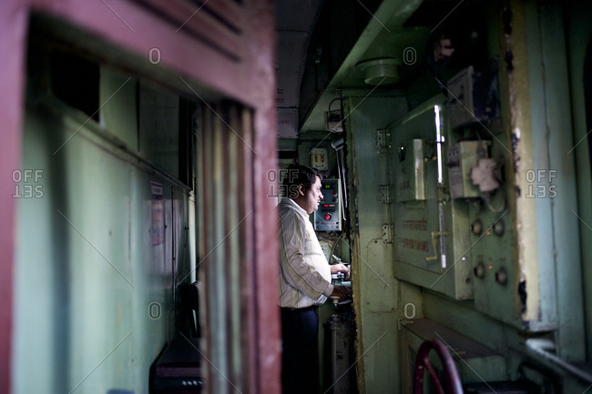 Mumbai, India - February 5, 2015: Railroad engineer driving a train