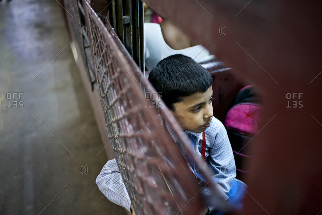 Mumbai, India - February 5, 2015: Child sitting by the window on a train