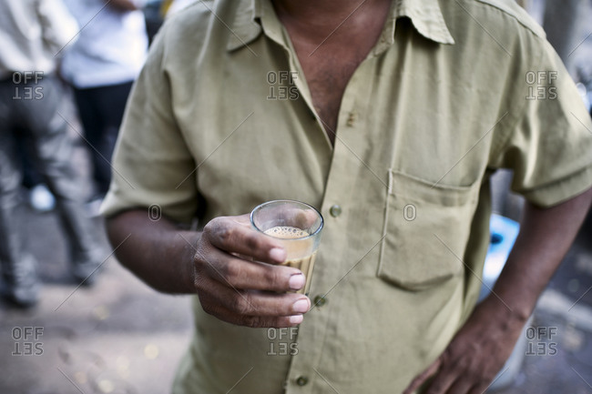 Close up of person holding a cup of masala chai tea