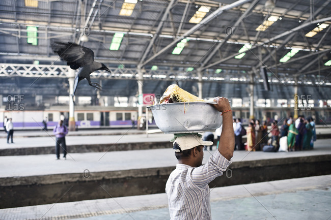 Mumbai, India - February 7, 2015: Crow follows a man carrying fresh fish