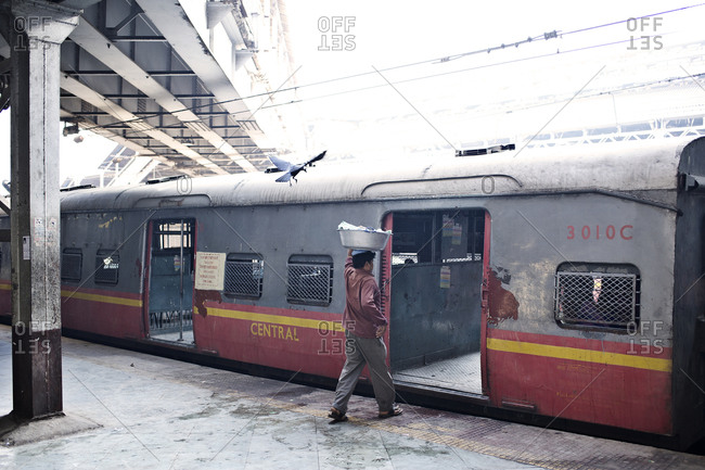 Mumbai, India - February 7, 2015: Man boarding a train with a crow following him