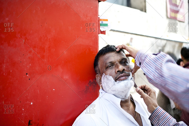 Mumbai, India - February 7, 2015: Men getting a shave on the street