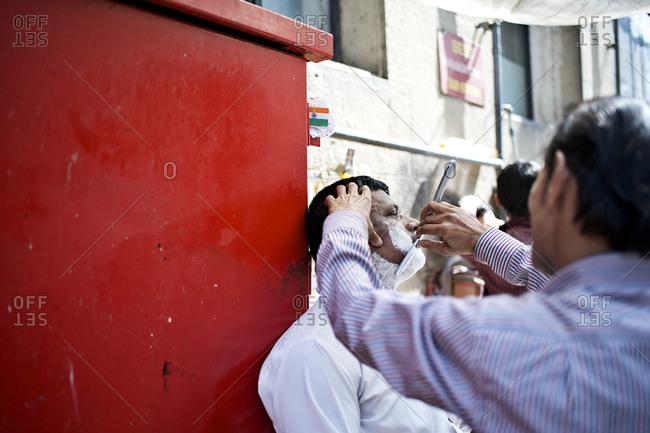 Mumbai, India - February 7, 2015: Street barber shaving a man