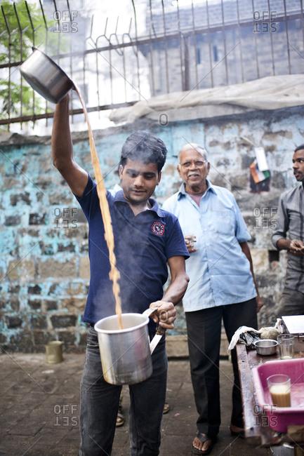 Mumbai, India - February 8, 2015: Tea vendor preparing masala chai