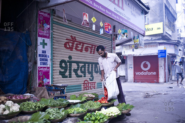 Mumbai, India - February 8, 2015: Man setting up vegetable stall in Mumbai, India