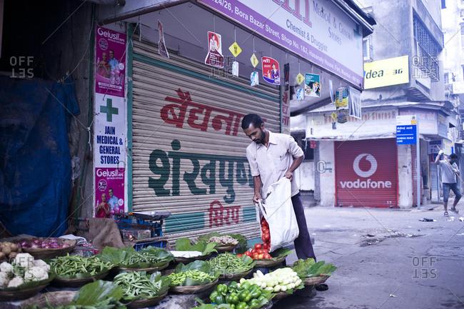 Mumbai, India - February 8, 2015: Man setting up vegetable stall in Mumbai, India