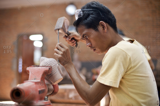 Siem Reap, Cambodia - December 20, 2014: Young man carving a Buddha head