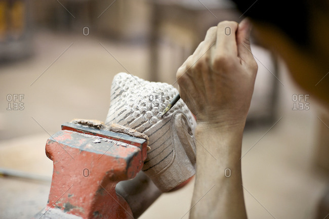 Person carving a figurine in a  workshop