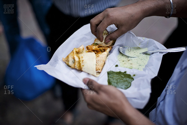 Person eating dosa with chutney