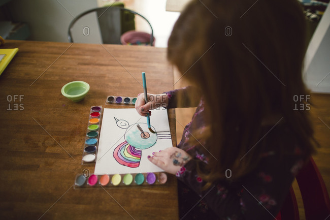 A little girl paints an imagined animal