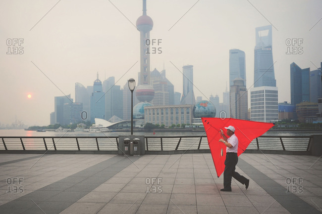 Shanghai, China - July 31, 2011: Man carrying a kite in front of the skyline