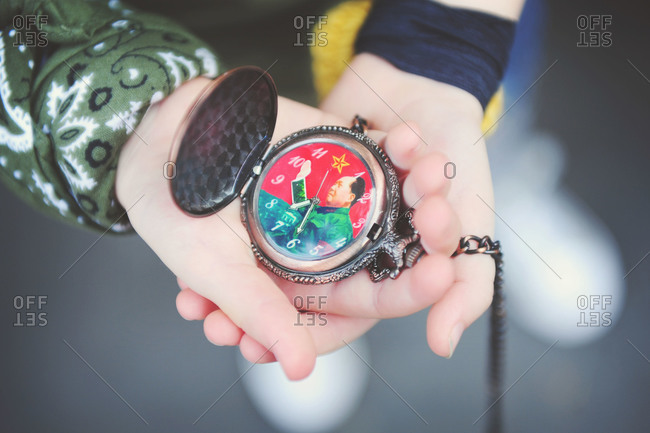 Hands holding Chairman Mao pocket watch