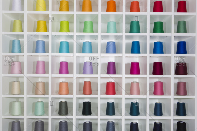 Large spools of brightly colored thread on shelf