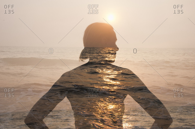Outline of woman's silhouette against beach sunset