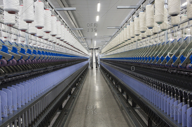 Machines in factory spinning wool into thread
