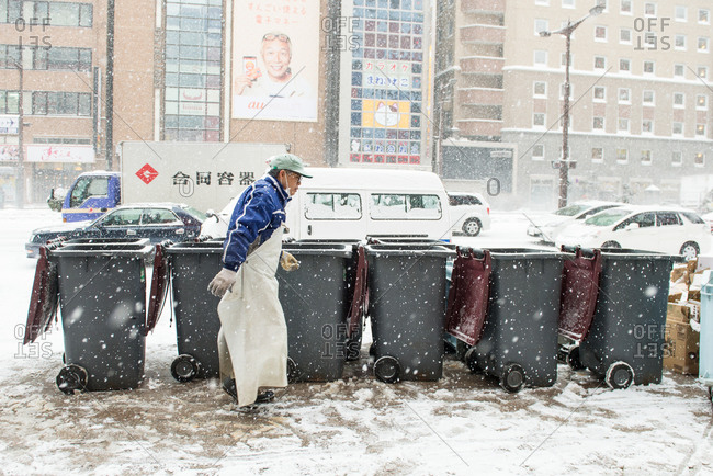 Sapporo, Japan - January 7, 2015: Man in apron walks past garbage cans in the snow