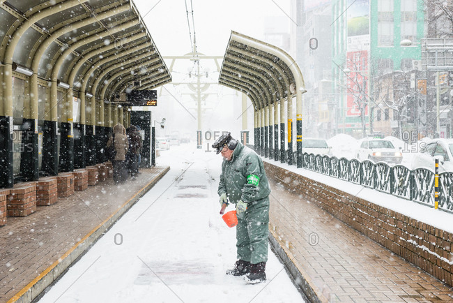 Sapporo, Japan - January 7, 2015: Man spreading salt at a snowy trolley stop in Japan