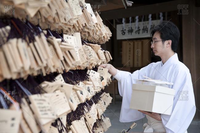 Tokyo, Japan -  March 30, 2012: Priest hangs wooden prayer tabs at shrine