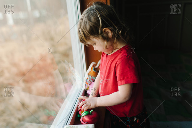 Girl playing with toys on bedroom windowsill