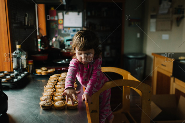 Girl lining up freshly baked muffins