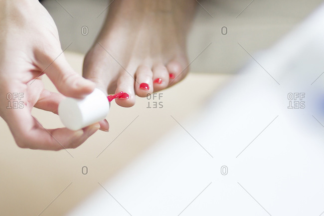 Woman painting her toenails pink