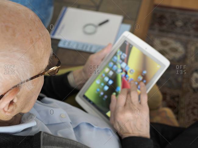 Old man at home using digital tablet
