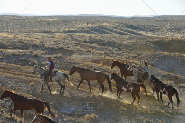 Cowboy and cowgirl leading horses in badlands