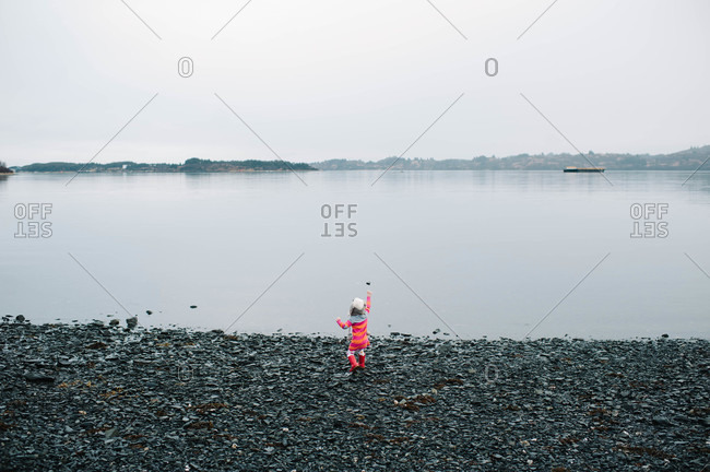 Young girl throwing stone on lake beach