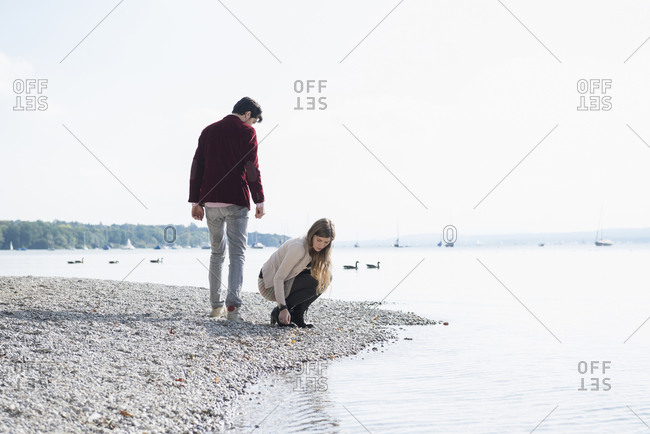 Young couple at the lake shore gathering pebbles