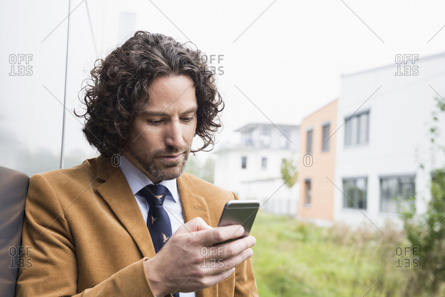 Man business in suit with cell phone reading an SMS