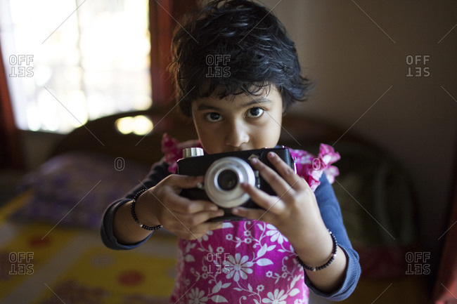 Little girl holding a camera