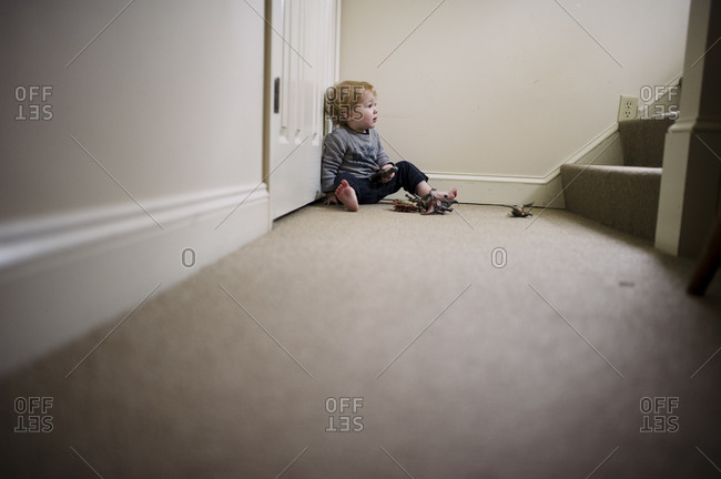 Toddler boy playing with toys at the bottom of the stairs