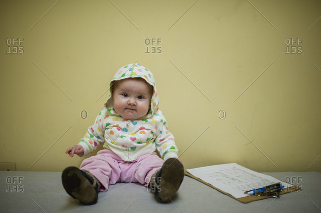 Baby girl sitting next to a clip board in doctor's office