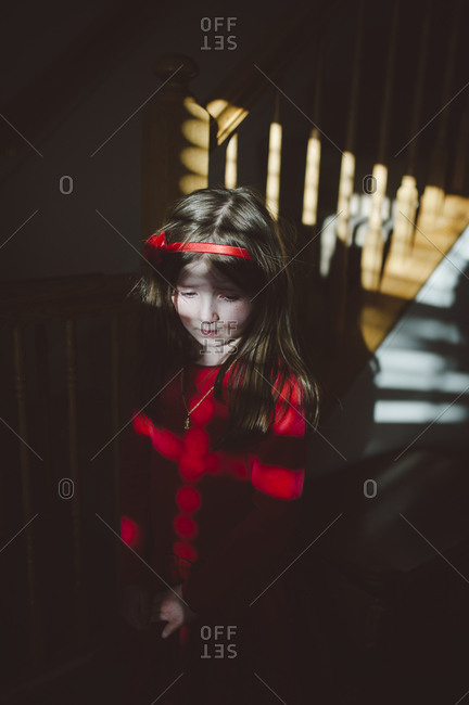 Moody child standing near dramatically lit staircase