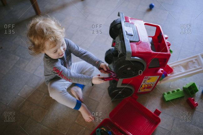 Toddler playing with a toy fire truck