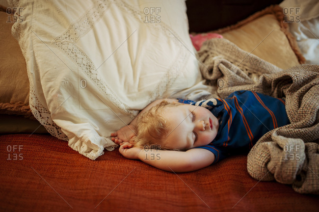 Young boy asleep on bed under blanket